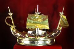 Golden crown in the shape of a ship on a red background stock photography