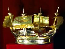 Golden crown in the shape of a ship on a red background royalty free stock image