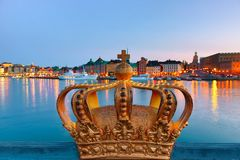 Golden crown on Skeppsholm bridge with illuminated Stockholm old city center Gamla Stan in the background during twilight sunset. stock photos