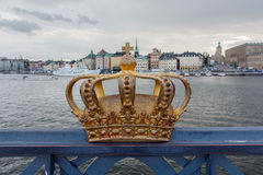Golden crown on Skeppsholm bridge with Stockholms slot (royal pa Royalty Free Stock Photo