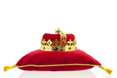 Golden crown on velvet pillow Stock Photos