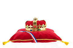 Golden crown on velvet pillow with Dutch flag Stock Photos