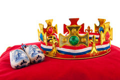 Golden crown on velvet pillow with Dutch wooden shoes. Golden crown on red velvet pillow for coronation with wooden shoes in Holland Royalty Free Stock Photography