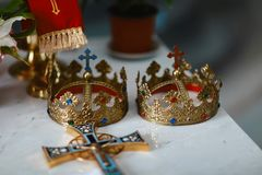 Golden crowns and wedding rings at the altar in the church at the wedding couple. traditional religious wedding ceremony.  Stock Photo