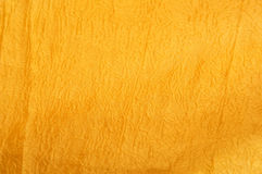 Golden crumpled fabric texture closeup. Background of a golden silk Royalty Free Stock Images