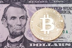 Golden cruptocurrency bitcoin on dollar banknote background. Royalty Free Stock Photo