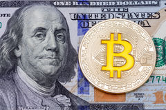 Golden cruptocurrency yellow `bitcoin on one hundred dollar bank. Note background. High resolution photo Royalty Free Stock Photo