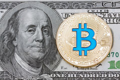 Golden cryptocurrency blue bitcoin on hundred dollar. Royalty Free Stock Images