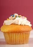 Golden cupcake with buttercream and sprinkles