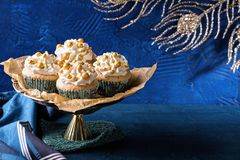 Golden cupcakes for christmas. On a blue background stock images