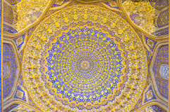 The golden cupola. SAMARKAND, UZBEKISTAN - APRIL 30, 2015: The carved plaster cupola decorated with gilt patterns on the bright blue background in mosque of royalty free stock photos