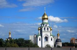 Golden cupolas of churches in Moscow. Modern living houses. Green trees. Blue sky with clouds background Royalty Free Stock Photo