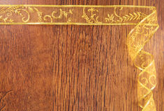 Golden curl ribbon frame  on wood Royalty Free Stock Image