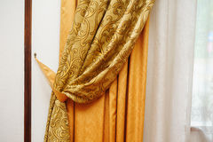 Golden curtain on the window in the room Stock Photos