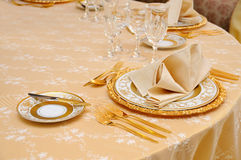 Golden cutlery with crystal glass Stock Photography