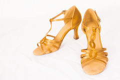 Golden dance shoes. Golden female dance shoes for latin dances on white background Royalty Free Stock Photography