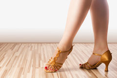 Golden dance shoes. Female legs are in golden latin dance shoes Royalty Free Stock Photography