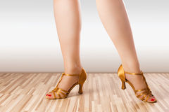 Golden dance shoes. Female legs are posing in golden latino dance shoes Stock Photography