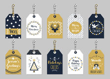 Golden and dark navy blue Christmas and Holiday gift tags set. On trendy gray background Stock Images