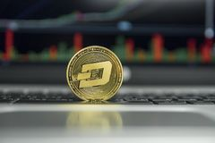 Golden Dash coin on a black keyboard of silver laptop and diagram chart graph on a screen as a background. Virtual. Cryptocurrency concept. Mining of dash stock photos