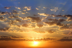 Golden dawn. The sun's rays paint the sky and clouds in golden color Stock Photography