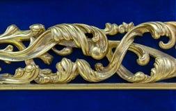 Golden decor element on a blue velvet background stock image