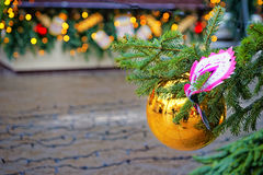 Golden decorating ball and mask on the christmas tree Royalty Free Stock Images