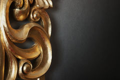 Golden decoration on dark wall. Part of golden stucco decoration in curve shape against dark wall with copy space Stock Images