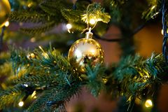 Golden decoration globe on christmas tree close up royalty free stock photos