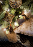 Golden decorations hanging on Christmas tree. Golden Christmas ball and brown and gold star with tassel hanging on spruce tree decorated with lights on blurred Royalty Free Stock Image