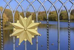 Golden decorative element at the forged fence royalty free stock photo