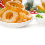 Golden deep fried onion rings. Served with mayonnaise dip and fresh vegetables oln background stock photography