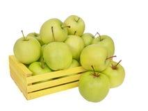 Golden- Delicious Äpfel stolpern aus dem gelben Kasten heraus, lokalisiert auf wh Lizenzfreie Stockfotografie