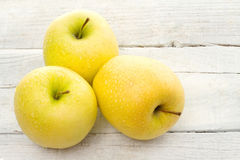 Golden delicious apple over white wood Royalty Free Stock Image