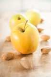 Golden delicious apples with almonds on wood. Three golden delicious apples with almonds on rustic wood stock photos