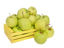 Golden Delicious apples tumble out of yellow box, isolated on wh Royalty Free Stock Photography
