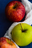 Golden delicious and royal gala apples with a white cloth against a blue background. Close up, selective focus Stock Images