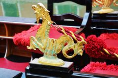 Golden detail of gondola, Venice, Italy. Vivid golden sea horse and red background, details of a gondola in Venice, Italy, Europe Stock Photo