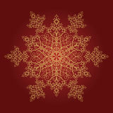 Golden detailed snowflake on red background Stock Photos