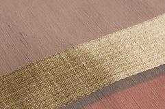 Golden diagonal stripe. On woven fabric, details Stock Photos