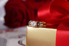 Golden diamond ring with gift box and red rose Royalty Free Stock Images