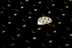 A golden dice showing six. Between a mess of black ones Royalty Free Stock Images