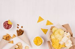 Golden different snacks on craft paper cone, triangles nachos, sauce in bowl on soft white wood background. Golden different snacks on craft paper cone Royalty Free Stock Photo