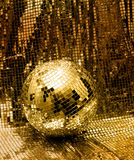 Golden disco mirror ball. Reflect light on glitter canvas background Royalty Free Stock Image