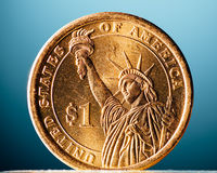 Golden dollar coin on blue background Stock Photography