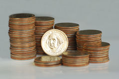 The golden dollar is surrounded by quarters. The golden dollar is surrounded by stacks of quarters Royalty Free Stock Photos