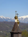 Golden dome of the church against blue sky. Golden domes of the Orthodox church, blue sky, spring nature and snow-capped mountains Stock Photography