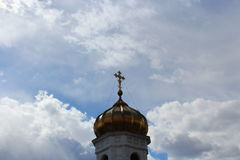 Golden dome of a church. Golden dome of a church with a cross on a blue background with clouds of sky stock photography