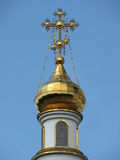Golden dome with a cross on blue sky background Stock Photo