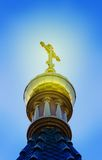 A Golden dome with a cross of the Church. On a cloudy sky background stock photography